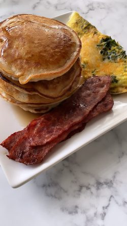 Fat stack of pancakes, kale omelette ans turkey bacon.