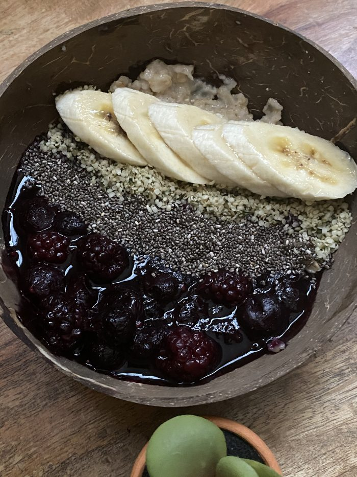 Oatmeal breakfast bowl. Topped with cooked berries, banana, chia seeds and hemp seeds.