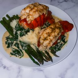 Broiled lobster, garlic mashed potatoes, lemon zest asparagus and Cajun cream sauce with spinach.
