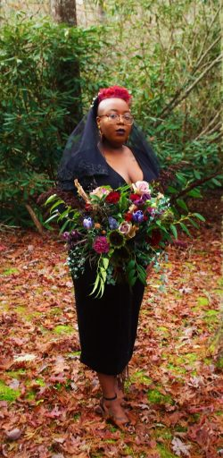 Moody and dark wedding bouquet crafted by Black-owned florist Crown Heritage Flowers, nestled in ...